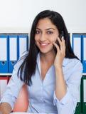 Γελώντας τουρκική επιχειρηματίας με το τηλέφωνο στο γραφείο Στοκ εικόνα με δικαίωμα ελεύθερης χρήσης