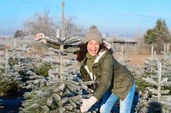 Γελώντας χαρούμενη γυναίκα που επιλέγει ένα χριστουγεννιάτικο δέντρο στοκ εικόνα