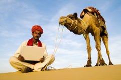 Γηγενές ινδικό άτομο με το lap-top του έξω σε μια έρημο στοκ εικόνα