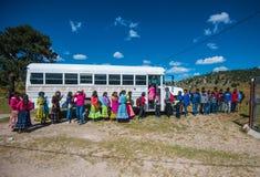 Γηγενείς σχολικοί σπουδαστές στο παραδοσιακό ζωηρόχρωμο φόρεμα με ένα σχολικό λεωφορείο, Μεξικό, Αμερική στοκ φωτογραφία