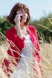Γηράσκουσα γυναίκα που σκέφτεται στο τηλέφωνο στα υψηλά λουλούδια θερινών τομέων Στοκ φωτογραφίες με δικαίωμα ελεύθερης χρήσης