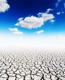 Γη και μπλε ουρανός ξηρασίας με τα σύννεφα Στοκ εικόνες με δικαίωμα ελεύθερης χρήσης