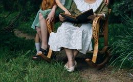 Γιαγιά επίσκεψης γιαγιά με τα εγγόνια της που κάθονται σε μια λικνίζοντας καρέκλα στον κήπο και που προσέχουν ένα παλαιό λεύκωμα  Στοκ εικόνα με δικαίωμα ελεύθερης χρήσης
