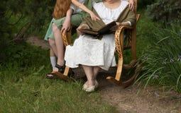 Γιαγιά επίσκεψης γιαγιά με τα εγγόνια της που κάθονται σε μια λικνίζοντας καρέκλα στον κήπο και που προσέχουν ένα παλαιό λεύκωμα  Στοκ Φωτογραφία