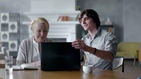 Γιαγιά διδασκαλίας εγγονών πώς να χρησιμοποιήσει ένα PC lap-top Χαμογελούν και γελούν φιλμ μικρού μήκους