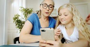 Γιαγιά και εγγονή με το αγκάλιασμα Smartphone απόθεμα βίντεο