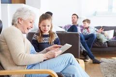 Γιαγιά και εγγονή που χρησιμοποιούν την ψηφιακή ταμπλέτα από κοινού στοκ εικόνες