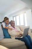 Γιαγιά και εγγονή που χρησιμοποιούν το lap-top στο καθιστικό Στοκ Εικόνες