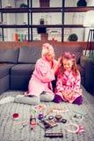 Γιαγιά και κορίτσι που φορούν τα μπουρνούζια που χρησιμοποιούν τους κυλίνδρους τρίχας το πρωί στοκ εικόνες