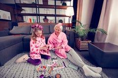 Γιαγιά και κορίτσι στα μπουρνούζια που κάθονται στο πάτωμα και που επιλέγουν hairpins στοκ φωτογραφία
