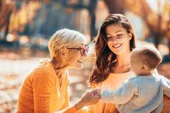 Γιαγιά και μητέρα που χαμογελούν στο μωρό στο πάρκο φθινοπώρου στοκ φωτογραφία με δικαίωμα ελεύθερης χρήσης