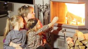 Γιαγιά και δύο μικρές εγγονές της που κάθονται από μια εστία στη οικογενειακή κατοικία τους στην παραμονή Χριστουγέννων απόθεμα βίντεο
