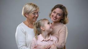 Γιαγιά, κόρη και εγγόνι που αγκαλιάζουν στο γκρίζο υπόβαθρο, σχέσεις ε απόθεμα βίντεο