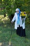 Γιαγιά με έναν κάλαμο και τα λουλούδια στοκ φωτογραφία με δικαίωμα ελεύθερης χρήσης