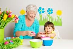 Γιαγιά με τα αυγά Πάσχας χρώματος εγγονών στοκ εικόνα