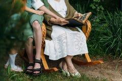 Γιαγιά με τα εγγόνια της που κάθονται σε μια λικνίζοντας καρέκλα στον κήπο και που προσέχουν ένα παλαιό λεύκωμα με τις φωτογραφίε Στοκ Εικόνα
