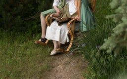 Γιαγιά με τα εγγόνια της που κάθονται σε μια λικνίζοντας καρέκλα στον κήπο και που προσέχουν ένα παλαιό λεύκωμα με τις φωτογραφίε Στοκ εικόνες με δικαίωμα ελεύθερης χρήσης