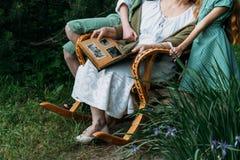 Γιαγιά με τα εγγόνια της που κάθονται σε μια λικνίζοντας καρέκλα στον κήπο και που προσέχουν ένα παλαιό λεύκωμα με τις φωτογραφίε Στοκ εικόνα με δικαίωμα ελεύθερης χρήσης
