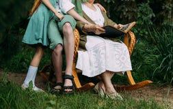 Γιαγιά με τα εγγόνια της που κάθονται σε μια λικνίζοντας καρέκλα στον κήπο και που προσέχουν ένα παλαιό λεύκωμα με τις φωτογραφίε Στοκ Εικόνες
