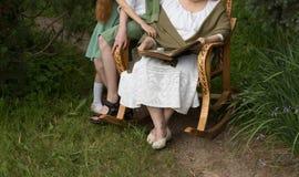Γιαγιά με τα εγγόνια της που κάθονται σε μια λικνίζοντας καρέκλα στον κήπο και που προσέχουν ένα παλαιό λεύκωμα με τις φωτογραφίε Στοκ φωτογραφίες με δικαίωμα ελεύθερης χρήσης