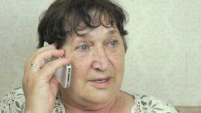 Γιαγιά που έχει μια κλήση στο κινητό τηλέφωνο στο εσωτερικό απόθεμα βίντεο