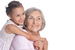 Γιαγιά που αγκαλιάζει με τη χαριτωμένη εγγονή της που απομονώνεται στο άσπρο υπόβαθρο στοκ φωτογραφία με δικαίωμα ελεύθερης χρήσης