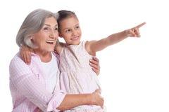 Γιαγιά που αγκαλιάζει με τη χαριτωμένη εγγονή της που απομονώνεται στο άσπρο υπόβαθρο στοκ φωτογραφία