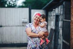 Γιαγιά που αγκαλιάζει την εγγονή στη φύση στην ηλιόλουστη θερινή ημέρα στοκ φωτογραφία με δικαίωμα ελεύθερης χρήσης