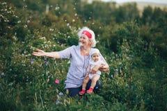 Γιαγιά που αγκαλιάζει την εγγονή στη φύση στην ηλιόλουστη θερινή ημέρα στοκ εικόνα