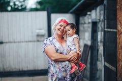 Γιαγιά που αγκαλιάζει την εγγονή στη φύση στην ηλιόλουστη θερινή ημέρα στοκ φωτογραφίες με δικαίωμα ελεύθερης χρήσης