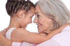 Γιαγιά που αγκαλιάζει τη χαριτωμένη εγγονή της που απομονώνεται με στοκ φωτογραφίες