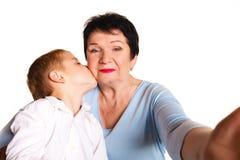 Γιαγιά που αγκαλιάζει τον εγγονό της σε ένα άσπρο υπόβαθρο και που κάνει selfie Στοκ Εικόνες