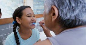 Γιαγιά που βοηθά την εγγονή για να βουρτσίσει τα δόντια της στο λουτρό 4k απόθεμα βίντεο