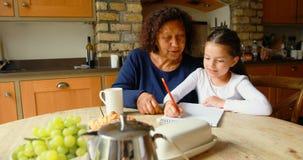 Γιαγιά που βοηθά την εγγονή στις μελέτες στην κουζίνα 4k φιλμ μικρού μήκους