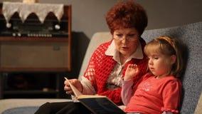 Γιαγιά που διαβάζει μια ιστορία στην εγγονή μωρών της απόθεμα βίντεο