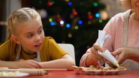 Γιαγιά που διακοσμεί τα μελοψώματα με τη ζάχαρη τήξης, μικρό κορίτσι που προσέχει αναστατωμένα φιλμ μικρού μήκους