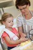 Γιαγιά που διδάσκει τα μπισκότα ψησίματος εγγονών της στοκ φωτογραφία