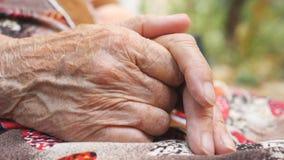 Γιαγιά που κάνει το μασάζ τα ζαρωμένα χέρια της έξω Ηλικιωμένη γυναίκα που φροντίζει την όπλα υπαίθρια Κλείστε επάνω την πλάγια ό φιλμ μικρού μήκους