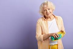 Γιαγιά που κρατά hosehold Ανώτερο καθαρίζοντας κύπελλο γυναικών που απομονώνεται στην πορφύρα στοκ φωτογραφία με δικαίωμα ελεύθερης χρήσης