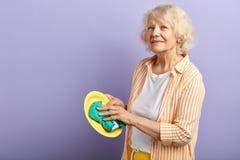 Γιαγιά που κρατά hosehold Ανώτερο καθαρίζοντας κύπελλο γυναικών που απομονώνεται στην πορφύρα στοκ εικόνα με δικαίωμα ελεύθερης χρήσης