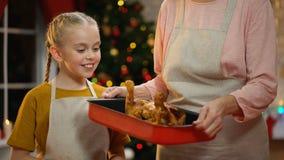 Γιαγιά που παρουσιάζει στο κορίτσι πικάντικο ψημένο κοτόπουλο Χριστουγέννων, προετοιμασίες για τις διακοπές απόθεμα βίντεο