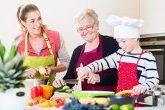 Γιαγιά, mum και γιος που μιλούν μαγειρεύοντας στην κουζίνα Στοκ Εικόνες