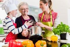 Γιαγιά, mum και γιος που μιλούν μαγειρεύοντας στην κουζίνα Στοκ φωτογραφία με δικαίωμα ελεύθερης χρήσης