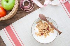 Γιαούρτι με το granola σε ένα κύπελλο, τη Apple και την ντομάτα στον ξύλινο πίνακα, Στοκ Φωτογραφίες