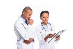 γιατροί αφροαμερικάνων στα άσπρα παλτά με τα στηθοσκόπια και τη διάγνωση, στοκ φωτογραφίες