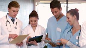 Γιατροί και νοσοκόμες που γράφουν τις σημειώσεις για τις περιοχές αποκομμάτων φιλμ μικρού μήκους