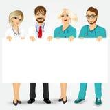 Γιατροί και νοσοκόμες που κρατούν έναν κενό πίνακα διαφημίσεων απεικόνιση αποθεμάτων