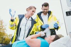 Γιατροί με την έγχυση και οξυγόνο που φροντίζει τη γυναίκα Στοκ Εικόνα