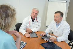 Γιατροί ομάδας που συναντούν και που παίρνουν τις σημειώσεις στο ιατρικό γραφείο Στοκ Εικόνες