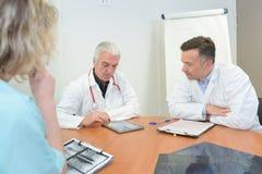 Γιατροί ομάδας που συναντούν και που παίρνουν τις σημειώσεις στο ιατρικό γραφείο Στοκ φωτογραφίες με δικαίωμα ελεύθερης χρήσης